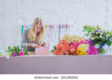 Professional woman floral artist, florist making gift box with flowers on table at workshop, flower shop. Floristry, holiday, birthday, handmade and small business concept