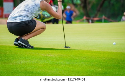 Professional woman golfer checking fairway and teeing golf in golf tournament competition at golf course for winner.