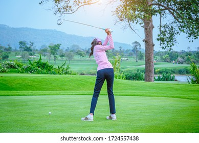 Professional woman golfer teeing golf in golf tournament competition at golf course for winner.