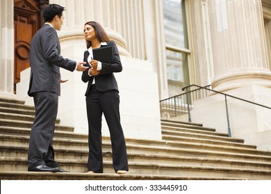 Professional woman and man having a discussion on the stairs of a stately building. Could be lawyers, business people etc.