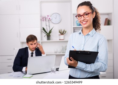 professional woman manager holding cardboard and smiling in office