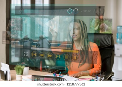 Professional woman operating a futuristic video screen in her office