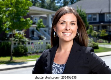Professional woman outside in a neighborhood looking into the camera.