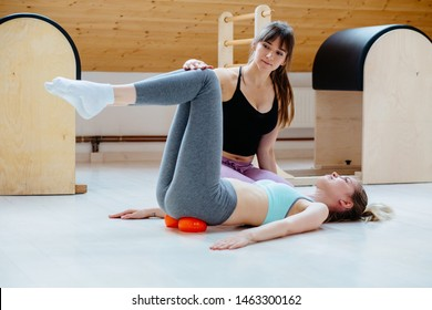 Professional woman physical therapist workout with client doing massage technique applying balls for pelvis or hip on sacroiliac joint pain area pain relief, lying on floor in pilates studio.