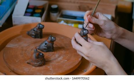 Professional woman potter, decorator painting ceramic souvenir penny whistle toy dog in pottery workshop, studio. Crafting, artwork and handmade concept