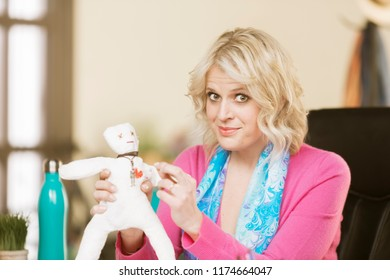 Professional woman putting a pin into the heart of a Voodoo doll