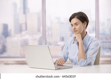 Professional woman sitting at skyscraper office working on laptop computer.