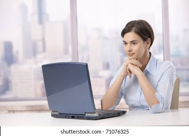Professional woman sitting at skyscraper office table, looking at laptop computer screen .?