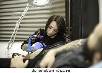 Professional woman tattooer working tattoo in a man leg. Tattoo studio.