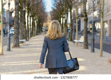 Professional woman walking away from the camera in town carrying her handbag along a tree lined pedestrian walkway in the street