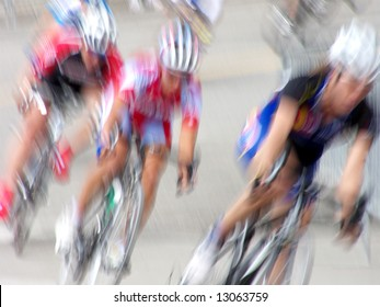Professional women bicycle racers round the bend - intentionally blurred