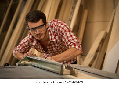 Professional woodworker sawing timbers with help of table saw. Serious and busy joiner working in safety glasses and checked shirt. Background of wood and lumbers in carpentry shop.