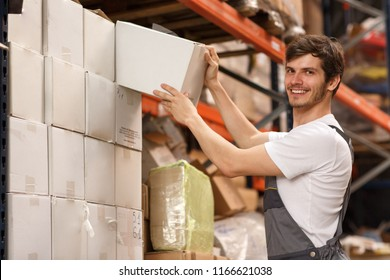Professional worker checking something while working in warehouse with lots of goods and boxes. Concentrated specialist standing, taking white box from shelf and looking at it.