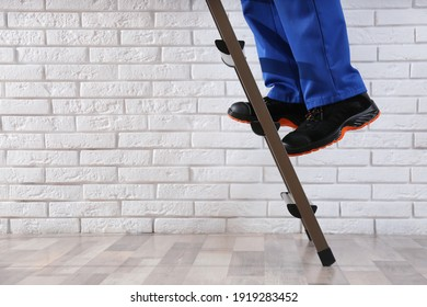 Professional worker climbing up ladder indoors, closeup. Space for text