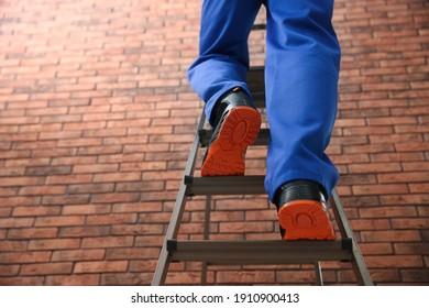 Professional worker climbing up ladder near brick wall, closeup. Low angle view