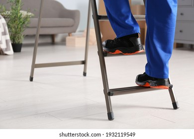 Professional worker climbing up ladder in room, closeup
