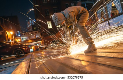 Professional worker cuts metal by electric saw. Fountain of sparks. Fire safety at construction site. Danger and hard work.