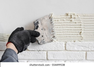 Professional worker gluing decorative tile on wall