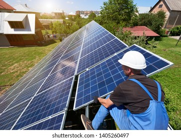 Professional worker installing solar panels on the green metal construction, using different equipment, wearing helmet. Innovative solution for energy solving. Use renewable resources. Green energy.