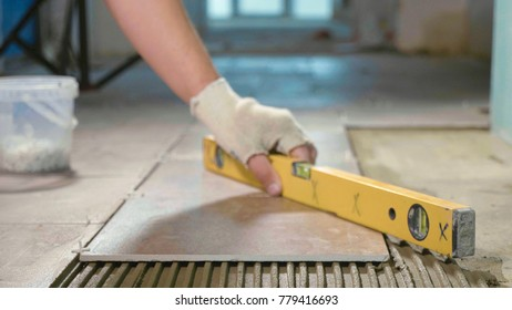 Professional worker laying tiles on floor at construction site close-up slow motion. Builder using construction level for aligning tile.