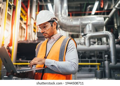 Professional worker of modern factory using laptop controlling program to automatic machinery. Engineering with laptop Programmable Logic Controller to manage large machine working full automatic.