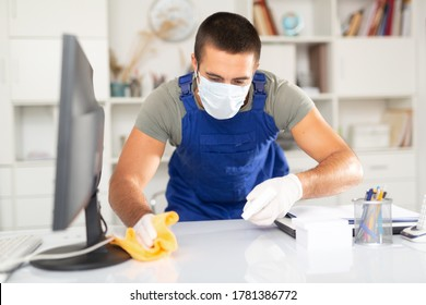 Professional worker of office cleaning service wearing protective face mask and rubber gloves wiping desk with disinfectant