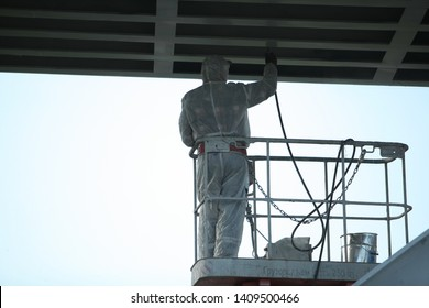 Professional worker in a protective suit and mask paints a bridge from the spray gun  stand on the hydraulic lift.