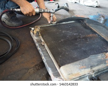 Professional worker repairing radiator cooling of car in garage workshop