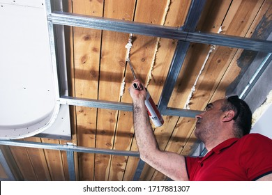 Professional worker uses mounting foam to close the cracks between boards on the ceiling