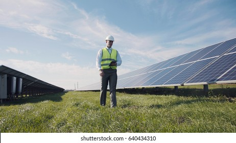 Professional worker walking along solar power station and using tablet.
