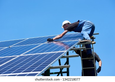 Professional workers team installing solar panels on the green metal construction using different equipment. Innovative solution for energy solving. Use renewable resources. Green energy.