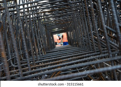 Professional workers wearing uniforms and helmets seen through steel bars reinforcement on a construction site.