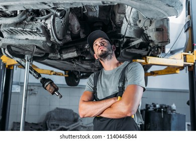 professional workman with crossed arms looking at car in mechanic shop