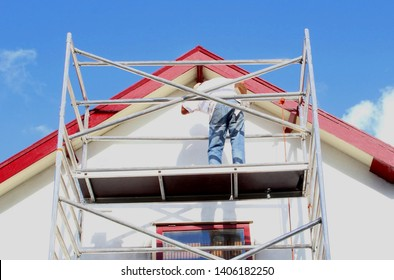 Professional workman is painting exterior walls and wooden window frames of ancient house at scaffold tower, outside home renovation under sunny blue sky.