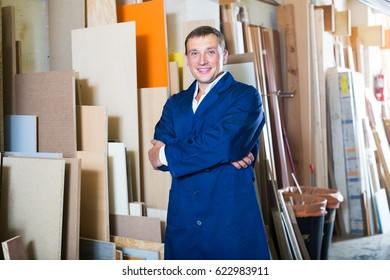 professional workman standing with plywood pieces in picture framing workshop
