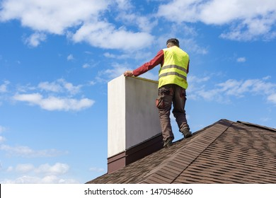 Professional workman standing roof top and measuring chimney of new house under construction against blue background
