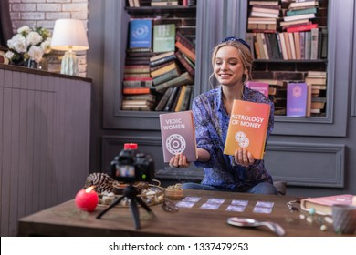 Professional writer. Positive joyful woman holding two books while showing them to the camera