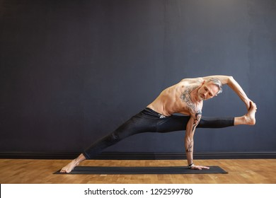 Professional yoga trainer makes challenging asanas showing a good stretch of the legs and arms on rug on floor against a dark background. Concept of longevity and youthful organism. Advertising space