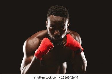 Professional young african fighter in boxing stance posing over black studio background