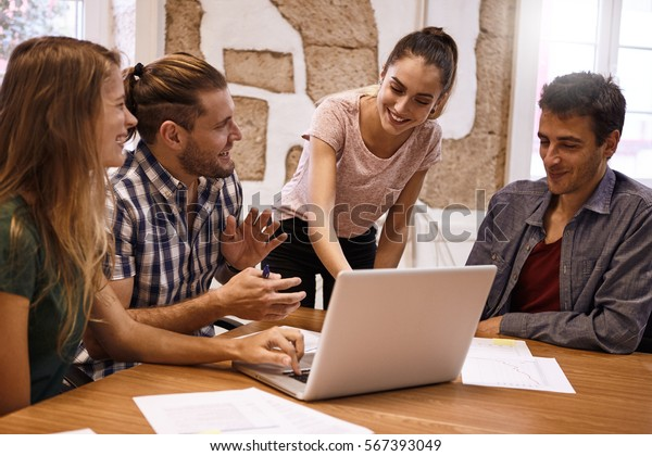Professional young business team in lively and exciting discussion while having a strategic planning meeting in a conference room at a desk with a laptop