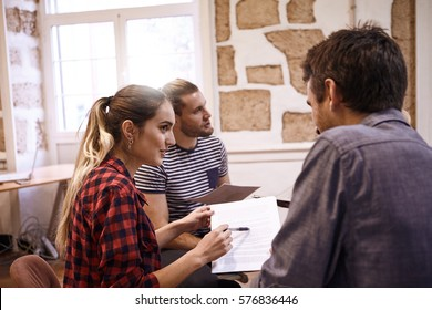Professional young business team sitting together in a circle with notes and pens in interesting discussion using pens as pointers