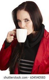 Professional young caucasian adult woman with long brown hair against a light background, wearing a black dress and red jacket, drinking coffee or tea