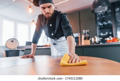 Professional young chef cook in uniform cleaning table on the kitchen.