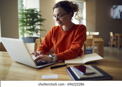 Professional young copywriter in trendy eyewear working on creation advertising content typing on laptop computer connected to wireless internet, skilled journalist browsing information in web site