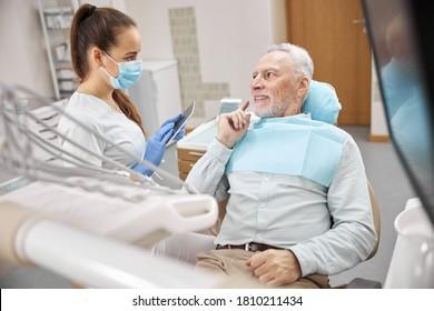 Berufstätige junge Zahnärztin, die eine Tablette hält und einen hohen Mann in einem Zahnstuhl während einer Beratung ansieht
