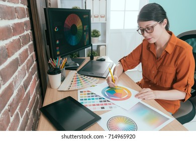 professional young female graphic designer choosing design color in office.