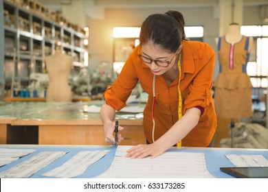 professional young female tailor cutter holding scissors along design pattern cut fabric for making clothing samples in factory system studio.