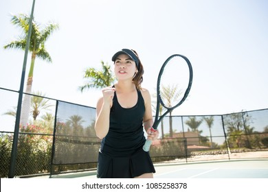 Professional young female tennis player with clenched fist celebrating after winning a game on court