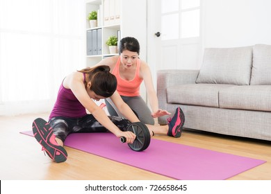professional young female trainer teaching girl student using ab wheel workout body and training muscle in living room at home.