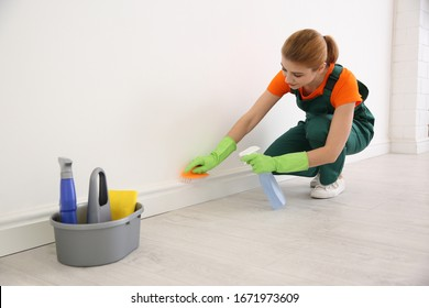 Professional young janitor in uniform cleaning room